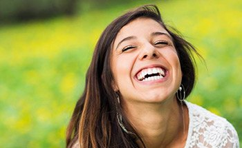 Laughing woman with flawless smile outdoors
