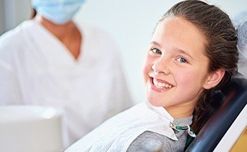 Smiling girl in dental chair
