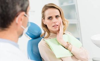 Woman at the dentist's office holding cheek