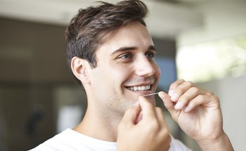 Man with bright smile flossing