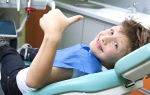 A child giving a thumbs-up at his dental appointment.