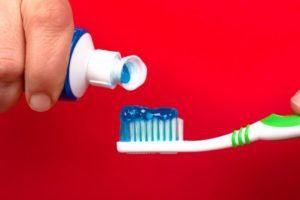 person squeezing toothpaste on a toothbrush